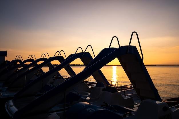 一日の終わりに湖に沈む夕日に岸に駐車した水上スクーターのシルエット。