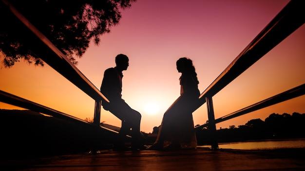 사랑의 키스와 저녁 하늘 배경으로 일몰 동안 함께 손을 잡고 웨딩 커플의 실루엣