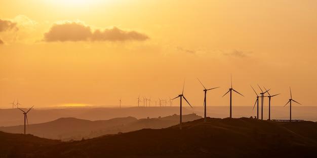 일몰에 재생 에너지를 생성하는 풍력 터빈 풍력 발전소의 실루엣