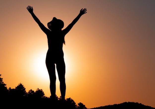 석양에 여자의 실루엣 힘의 개념과 목표 복사 공간을 극복