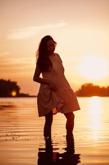 日没時の女性のシルエット長い茶色の髪が立っているセクシーな美しい女性のロマンチックな写真...