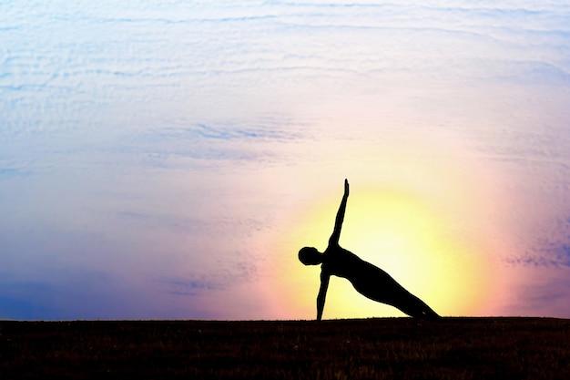 Силуэт женщины на закате. йога, фитнес и здоровый образ жизни.