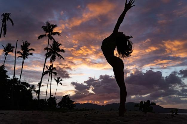 Силуэт женщины во время тропического захода солнца с пальмой и драматическими облаками. концепция отдыха и курорта.