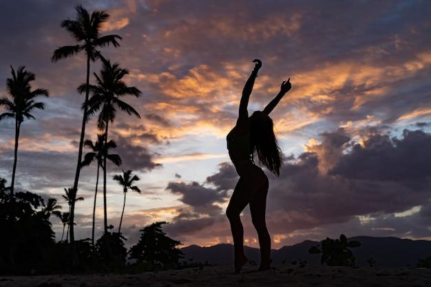 Силуэт женщины во время тропического захода солнца с пальмой и драматическими облаками.