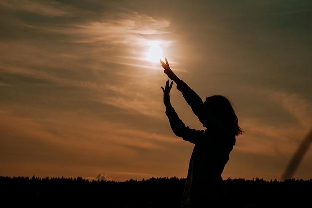 夕日を楽しむ女性のシルエット。麦畑の女性が流れるような動きをします。落ち着きと瞑想の概念