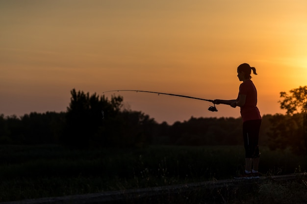Силуэт женщины, ловящей рыбу на берегу реки