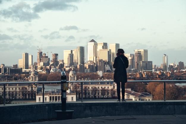 日没時、イギリスのロンドン市を後ろから見ている女性のシルエット
