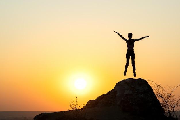 夕暮れ時、空の岩の上だけでジャンプ女性ハイカーのシルエット