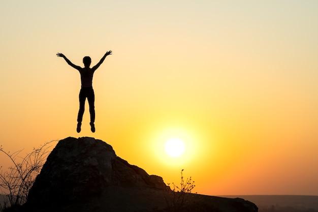 산에서 일몰에 빈 바위에 혼자 점프 여자 등산객의 실루엣. 저녁 자연에 절벽에 서서 그녀의 손을 올리는 여성 관광. 관광, 여행 및 건강한 라이프 스타일 개념.