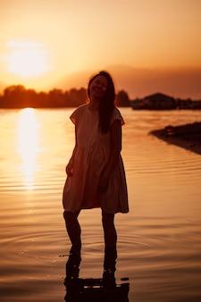 夕焼けの光線の女性のシルエット光線の水に立っている若い美しい女性のロマンチックな写真...