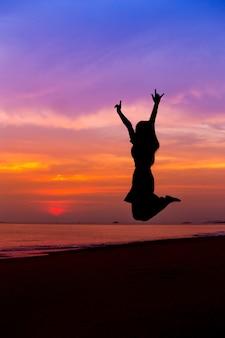 Силуэт женщины, прыжки с поднятыми руками на морском пляже на закате