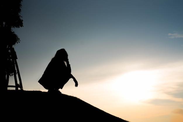 Силуэт женщины в поисках концепции на закате