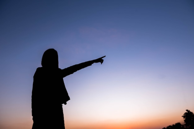 空に指で指す女性のシルエット