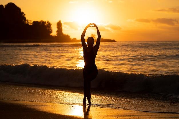ビーチでポーズをとる女性のシルエット