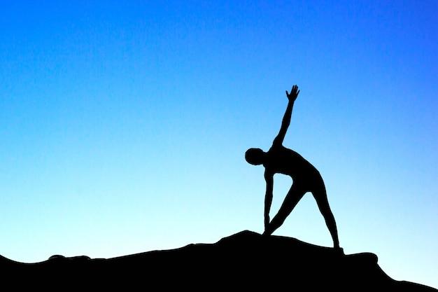 Силуэт женщины, практикующие йогу при солнечном свете