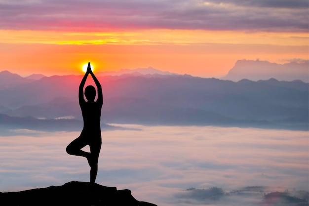 日の出、ヨガを練習している女性のシルエット