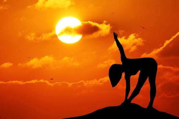 Силуэт женщины, практикующей йогу во время заката на берегу моря.
