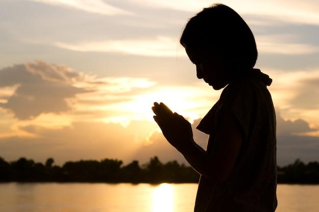 Силуэт женщины молятся на фоне прекрасного заката.