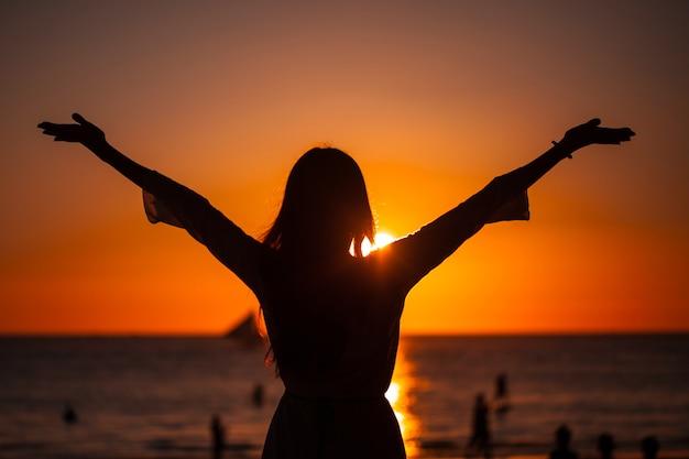 바다 위에 황금 일몰에 팔을 올리는 여자의 실루엣. 자유, 성공 및 희망 개념