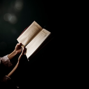 Silhouette of woman reading in quran