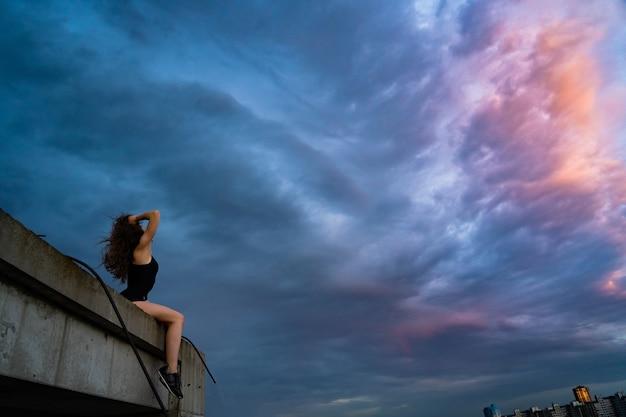 꿈의 기회와 기회의 일몰 개념 동안 극적인 하늘에 옥상 가장자리에 앉아있는 여자의 실루엣