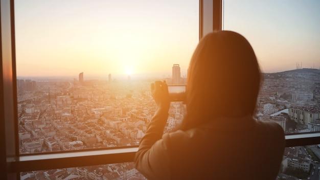 Силуэт женщины, фотографирующей панорамный вид на город на закате на смартфоне, фокусируется на городе