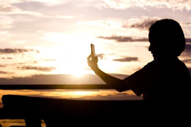 スマートフォンを使用して女性のシルエットは、美しい夕日の背景に写真を撮る。