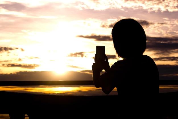 スマートフォンを使用して女性のシルエットは、美しい写真を撮る