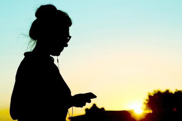 일몰의 배경에 휴대 전화와 헤드폰을 가진 여자의 실루엣. 소셜 미디어와 자연