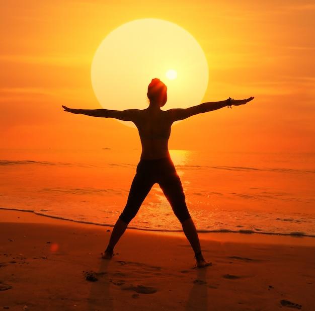 Силуэт женщины с солнцем позади