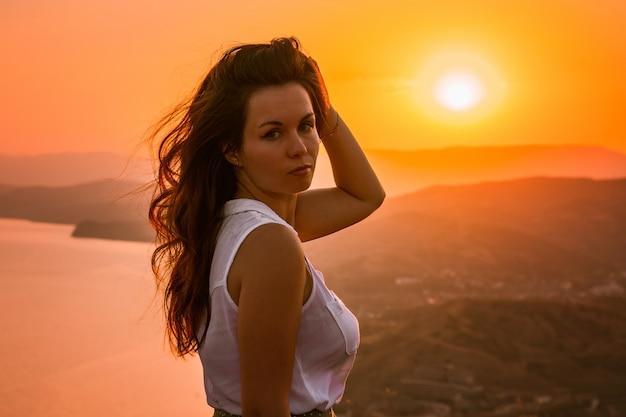 Силуэт женщины на оранжевом закате на скале с видом на горы