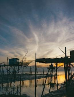 日没時に海の近くの木製のスタンドのシルエット