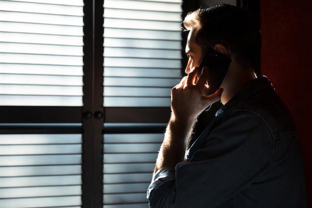 Силуэт молодого привлекательного человека разговаривает по мобильному телефону, стоя в темной комнате против солнечного света из окна на теневых жалюзи