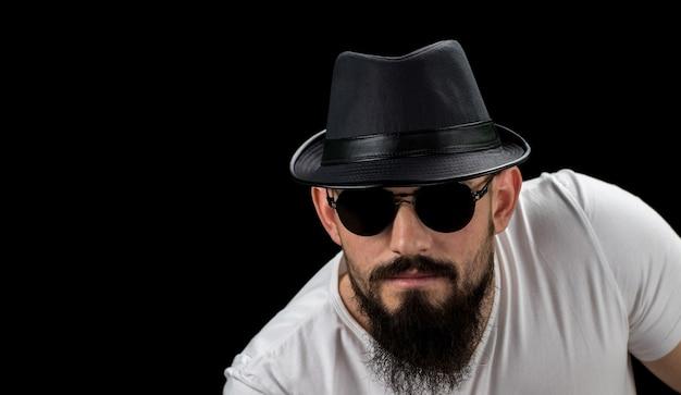 Силуэт молодого уверенно красивого бородатого хипстера человека в шляпе и солнечных очках. студия снята на темном фоне изображение с свободной копией пространства. Premium Фотографии