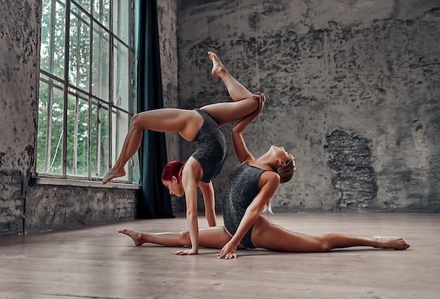 Силуэт молодой прохладной привлекательной женщины-йоги, практикующей концепцию йоги, стоя в упражнении адхо мукха врикшасана, в позе дерева лицом вниз и другая девушка сидит в шпагате.