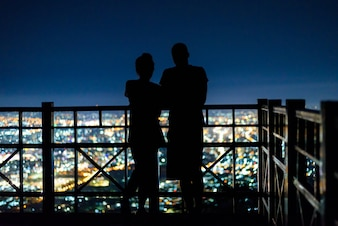Silhouette of young couple stand on mountain view point in midnight