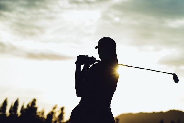 Силуэт молодой женщины-игрока в гольф ударил подметать и держать поле для гольфа, делая качели для гольфа, она делает упражнения для отдыха