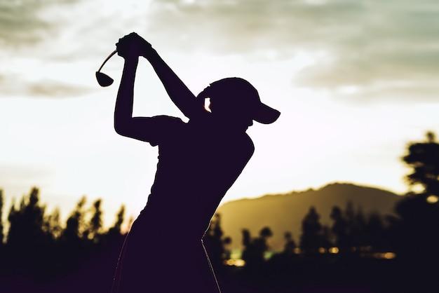 Силуэт молодой женщины-игрока в гольф ударил подметать и держать поле для гольфа, делая качели,