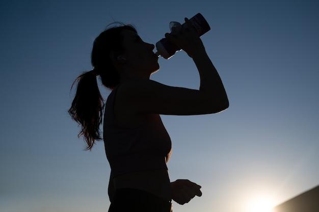 선글라스를 쓴 젊은 피트니스 여성의 실루엣은 도시에서 달리기를 마칩니다. 물을 즐기십시오. 일몰. 건강한 생활. 자유. 야외 운동.