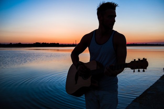 日の出中に海辺でギターを弾く若いハンサムな男のシルエット