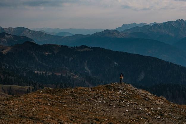 秋の山の若い男性のヒップスターのシルエット。ディスカバリートラベルデスティネーションコンセプト。高い岩の背景の観光客。スポーツとアクティブライフのコンセプト。