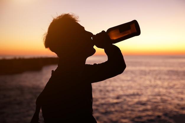 ボトルの海と背景に夕日からワインを飲む若い男のシルエット