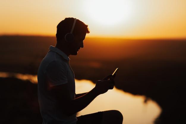 Силуэт молодого человека, держащего мобильный телефон. он наслаждается закатом и слушает музыку на смартфоне.