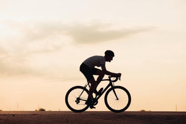 스포츠 복장 및 일몰 동안 포장 도로에 자전거를 타고 헬멧에 젊은 남자의 실루엣