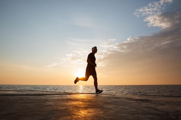 Силуэт молодого человека в спортивных шортах и футболке, бегущего вдоль пирса на берегу и слушающего музыку через беспроводные наушники во время восхода солнца