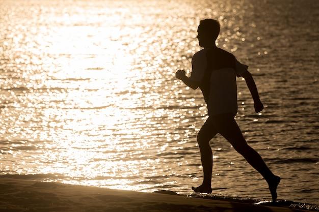 해변에서 조깅하는 젊은이의 실루엣