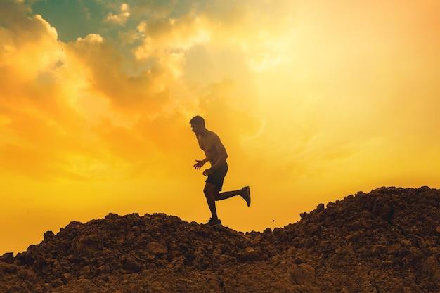 산 건강 및 라이프 스타일 개념의 상단에 흔적을 실행하는 젊은 남자 러너의 실루엣