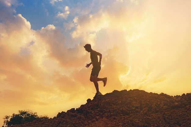 산 정상 건강 및 라이프 스타일 개념의 흔적을 실행하는 젊은 남자 주자의 실루엣