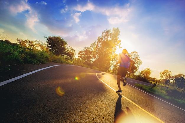 야외 운동 중 도로 피트 러너 피트니스 주자에서 역주를 실행하는 젊은 남자의 실루엣