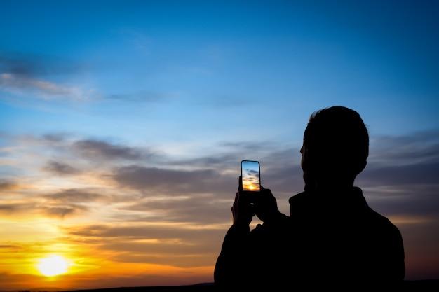 Силуэт молодого человека снимает закат на телефоне, смартфон. путешествия, прогулки.